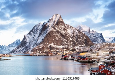 Mountains and sea bay on the Lofoten islands, Norway. Houses near mountains. Night winter landscape with mountains and town in the sea bay. Natural background in the Norway