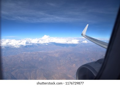 Mountains seen through the window of an airplane. Wing of the airplane landing at the airport seen through the window. Andes mountain in the background. Peruvian Andes