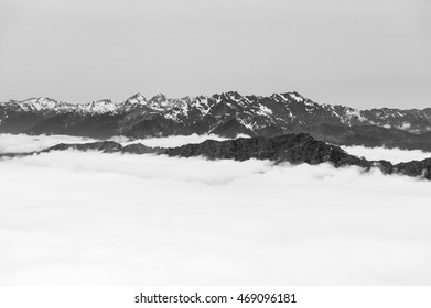 Mountains shrouded by clouds in black and white