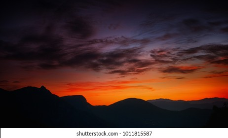 mountains silhouetted in front of an orange horizon