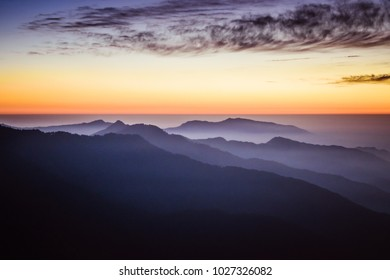 Mountains silhouettes view colorful landscape with twilight sky & red sunset light rays over foggy mountain during sunset at Indian Himalayas from Nag Tibba base camp, Uttarakhand India.