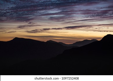 Mountains silhoutted by colorful sunset