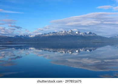 Mountains with snow are reflected in the water under blue sky