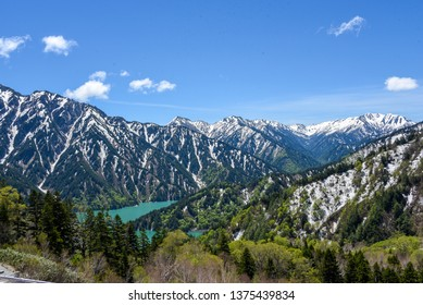Mountains with Snow Surrounding Kurobe Lake in Toyama Prefecture, Japan under Blue Sky on Tateyama Kurobe Alpine Route in Toyama Prefecture, Japan