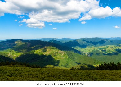 Mountains in summer sunny day with blue sky and white clouds