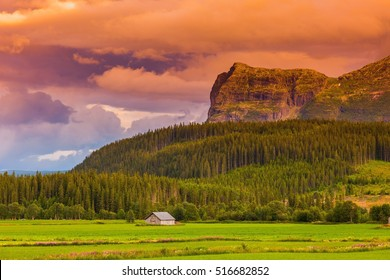 Mountains at sunset nature landscape. House in the norwegian village at forest.  Beautiful scenery autumn sky. Green colorful Norway, Europe. Rural hills morning background. Scenic summer valley view.