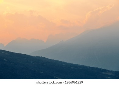 Mountains at sunset near Santa Croce Lake. Cloudy sky. Province of Belluno, Italy