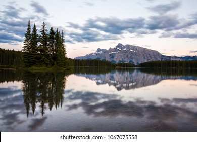 Mountains and surrounding coniferous forests reflected in the tranquil water of Two Jack Lake, Banff National Park, Alberta, Canada under a cloudy sky at sunset or sunrise with a pink glow to the sky