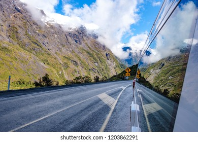 Mountains and their reflection in the side of a campervan