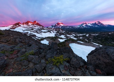 The mountains of the Three Sisters Wilderness glow during a vibrant sunrise in Central Oregon.