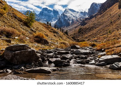 Mountains valley landscape: cold brook with many rocks, red grassy hill slopes and mountain peaks (including Monte Viso) in the background. Queyras Regional Park, France, Europe.