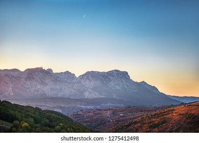 Mountains view with hairpin turn road with aircraft trail in sky and mountains background, Durmitor on the way to Black Lake - Crno Lake, from Zhablyak, beauty sunset orange colors