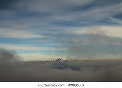 Mountains in winter far away surrounded by clouds and mist