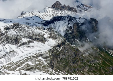 A mountainscape near Schilthorn, with rocks, snow and clouds.
