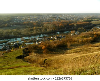 Mountainside, houses, river and woods. View from above. Autumn landscape