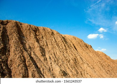 Mountainside with ravines from the rain. Blue sky and sand-colored mountainside.