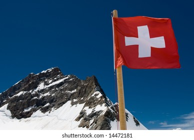 A mountaintop view of the national flag of Switzerland with the Jungfrau in the background