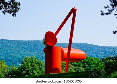 "Mountainville, New York/United States-7/7/2019: beautiful view of red steel sculpture of ""Adam"" by Alexander Liberman with mountain in the background"