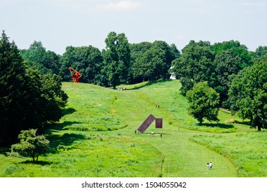 "Mountainville, New York/United States-7/7/2019: beautiful scenery of meadow path to the sculpture of ""suspended"" by Menashe Kadishman and ""Adam"" by Alexander Liberman"