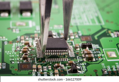 Mounting microchip on green electronic circuit board with tweezers
