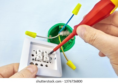 Mounting of new button for double light switch with help of screwdriver, electrical work.