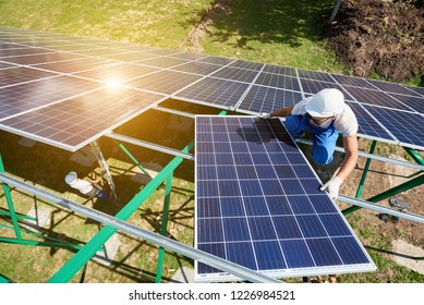 Mounting solar batteries on green metallic carcass. Risky work, needing special equipment. Innovative high-tech exterior. Modern solution for natural resources saving, using renewable solar energy.