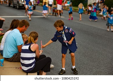 Mountville, PA, USA - May 30, 2012:  At the old-fashioned, small town America parade, a  Boy Scout gives an US Flag to a child during  the Memorial Day observance.