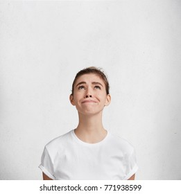 Mournful frustrated female dressed in white casual t shirt looks upwards, tries not to cry, asks God for help, isolated over white concrete wall with copy space. Vertical shot. Cheerless woman