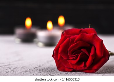 Mourning concept. Close up of  red rose and burning candles on grey textured background. Card for mourning, death, sorrow.Selective focus. Place for text.
