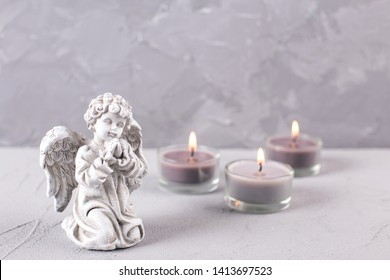 Mourning concept. Little angel and burning candles on grey textured background. Card for mourning, death, sorrow.Selective focus. Place for text.
