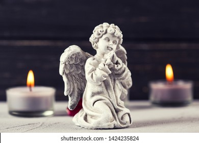 Mourning concept. Little angel and burning candles on  dark background. Card for mourning, death, sorrow.Selective focus.