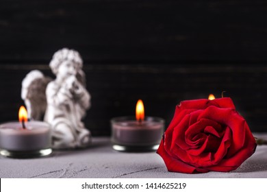 Mourning concept. Little angel, red rose and burning candles on  dark background. Card for mourning, death, sorrow.Selective focus is on rose. Place for text.