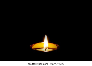 Mourning Condolence Memorial funeral cremation ceremony concept. Single burning isolated candle light on  black background. Dark. Peace.