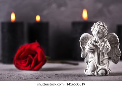 Mourning  layout. Little angel, red rose and burning candles on grey textured background. Card for mourning, death, sorrow.Selective focus. Place for text.