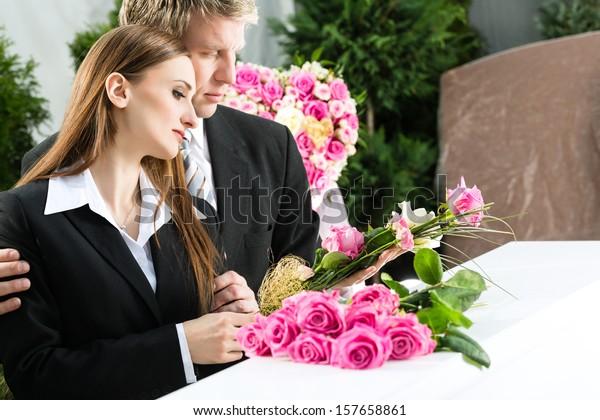 Trauerende Mann und Frau auf der Beerdigung mit rosafarbener Rose im Korb oder Sarg