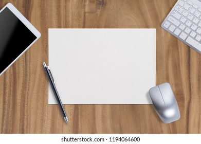 Mouse one Blank Paper with Tablet Keyboard and Pen  on wood table background.Copy space