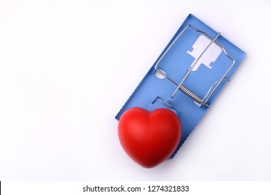 A mousetrap with a big red heart. Symbol of toxic love, difficult love, relationship, blind love, dangerous love.