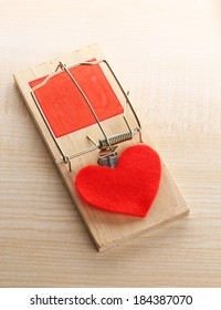 Mousetrap with heart on wooden background