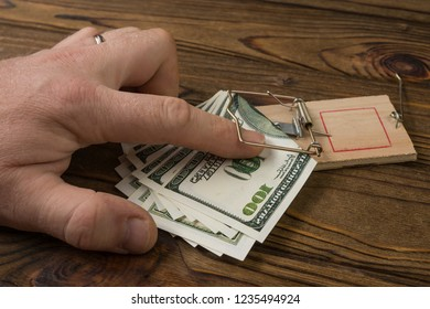 mousetrap, human hand, us dollar bills on wooden background. financial trap. - Shutterstock ID 1235494924