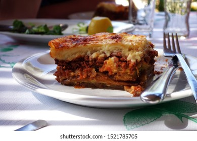 moussaka with aubergine on a dish. traditional greek meal on a rustic table