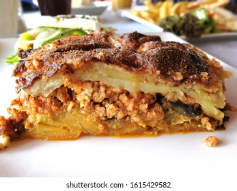 moussaka close-up side view. Traditional Greek dish of baked layers, eggplant, meat, potatoes Bechamel sauce