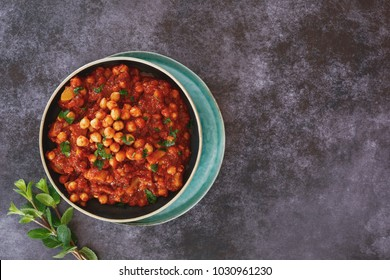 Moussaka eggplant with chickpea. Maghmour, traditional Lebanese vegetarian eggplant stew with chickpeas, garlic, onions, and tomatoes. Top view, blank space, dark toned image