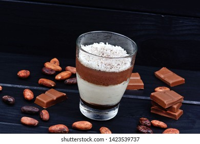 Mousse of chocolate in a glass jar on black wooden table