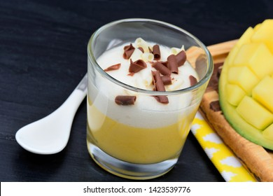 Mousse of mango with chocolate in a glass and mango cubes on black wood table