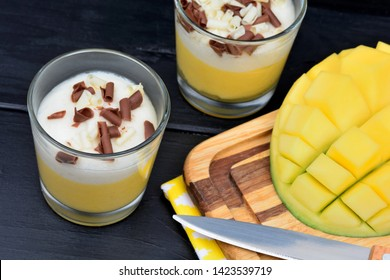 Mousse of mango with chocolate in a glasses jar on a wood table
