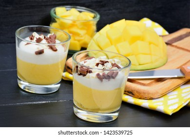 Mousse of mango in a glass jars on a wooden table