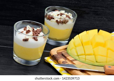 Mousse of mango in a glasses on black wood table