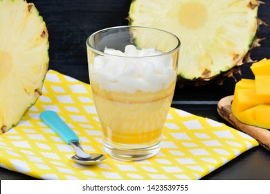 Mousse of pineapple fruit and mango in a glass jar on a wood table
