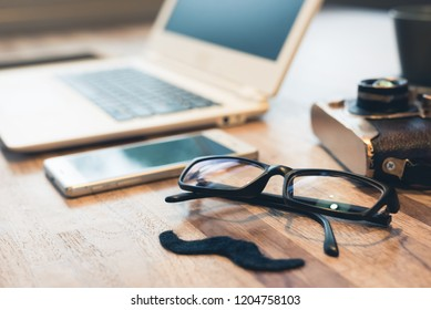 moustache and glasses with laptop on table
