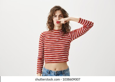 Moustache would suit me if I were guy. Childish woman with curly hairstyle and in cropped top making faces and frowning while holding index finger above nose, making facial hair, acting like man